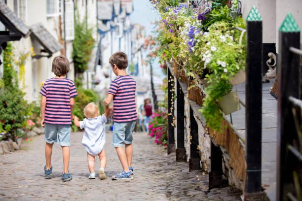 Hermosa familia, caminando por las calles de Clovelly, bonito pueblo antiguo en el corazón de Devonshire - foto de stock