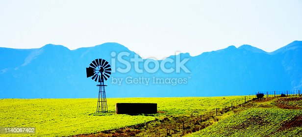 Old style windmill stands with little concrete dam in a field of crops on an beautiful farm with a blue-tinged mountain range in the background.