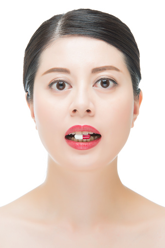 Beautiful Fashion Asian Woman Bite Medicine Pill For Medical Stock Photo -  Download Image Now - iStock
