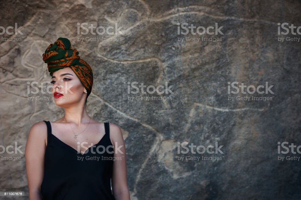 Beautiful fashion east woman portrait with oriental accessories and colorfull shawl on head on the background of rock paintings. stock photo