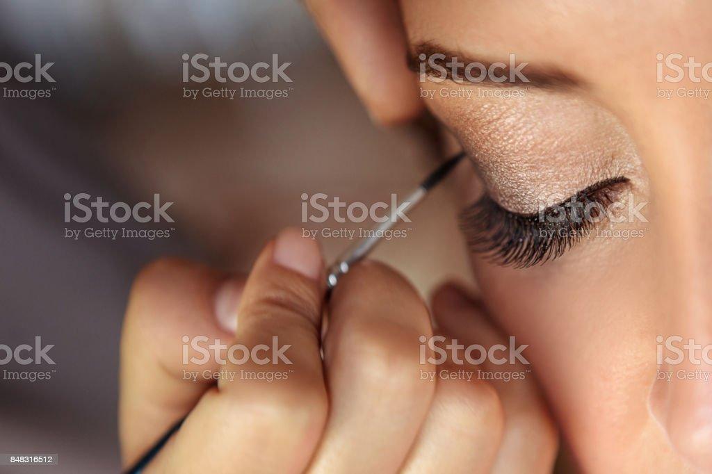 Beautiful fashion model applying makeup by makeup artist. stock photo