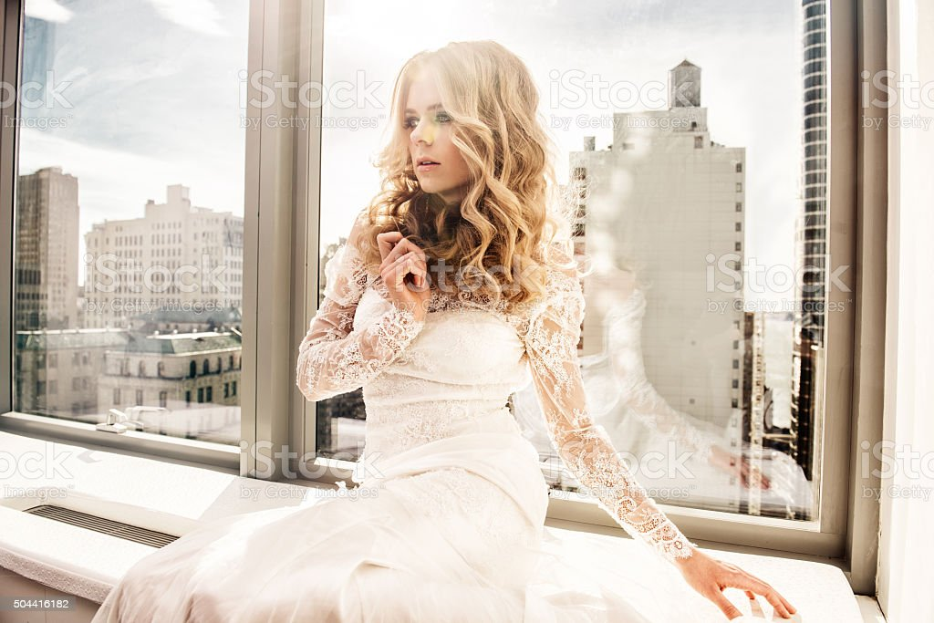 Beautiful fashion model bride sitting near the window stock photo