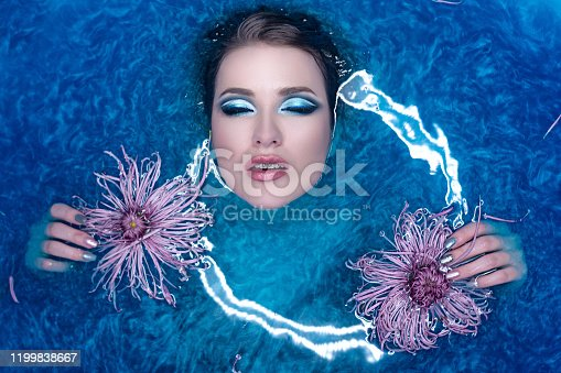 Beautiful fashion model girl taking blue bath, spa and skin care concept. Young woman with bright makeup and pink flowers relaxing in blue bath. Healthy Face and hands.