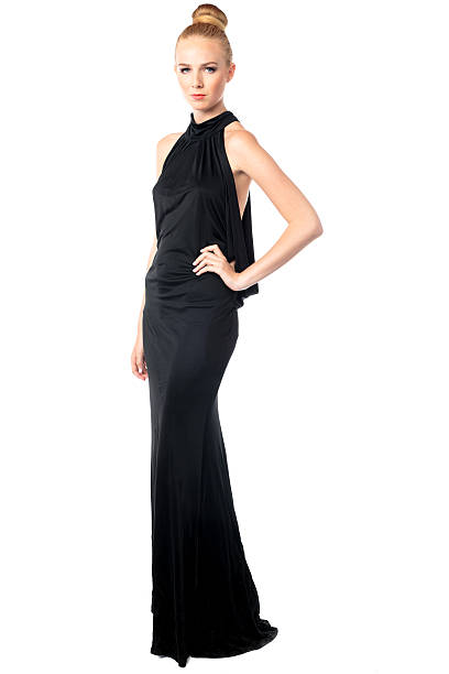 Beautiful fashion model in an evening gown Beautiful elegant fashion model posing in a long black stylish evening gown with her hand on her hip and a serious expression, isolated on white evening wear stock pictures, royalty-free photos & images