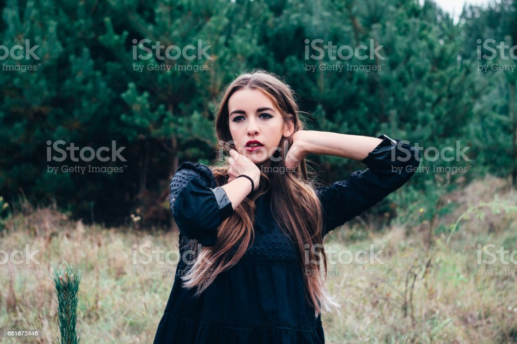 Beautiful fashion model posing in the autumn park on a background of trees stock photo