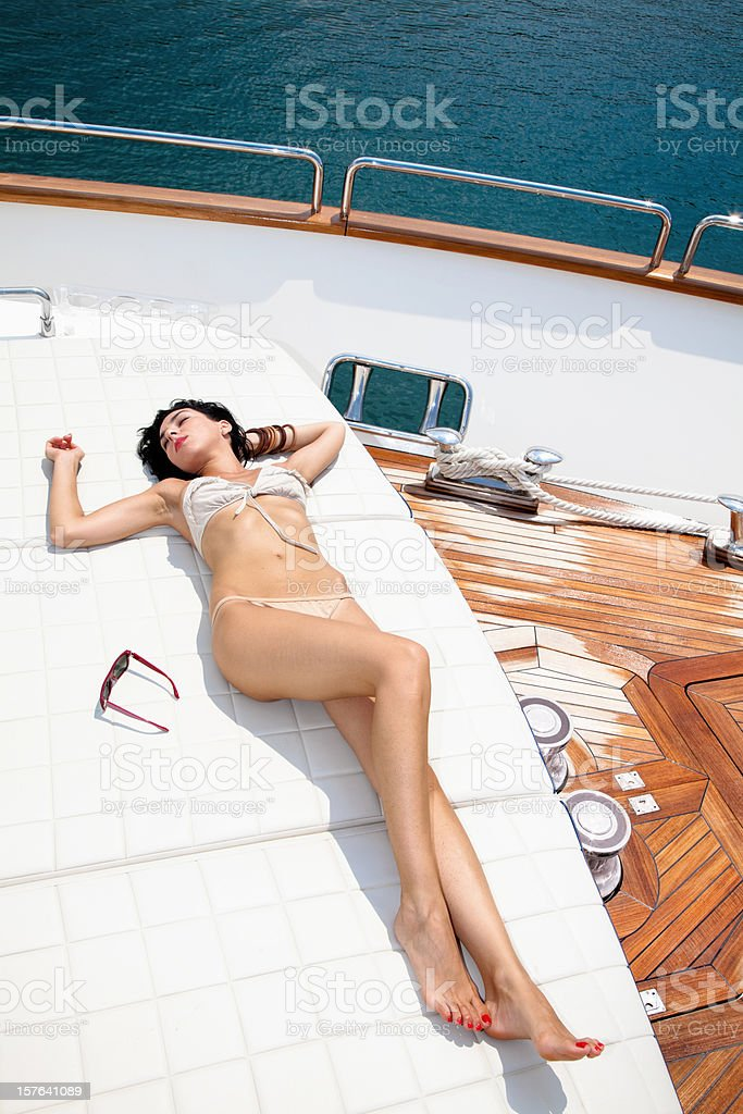 Beautiful fashion model sunbathing and relaxing on a luxury yacht royalty-free stock photo