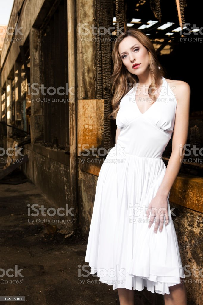 Beautiful Young Woman Fashion Model in White Dress, Burned Building royalty-free stock photo