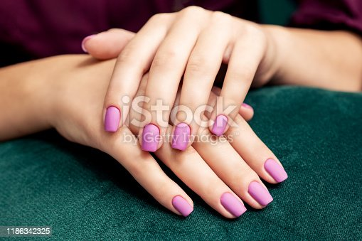 Beautiful purple matte manicure on the woman's nails on a dark green fabric background close up.