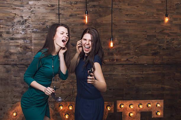 Beautiful fashion women girlfriends singing while listening stock photo
