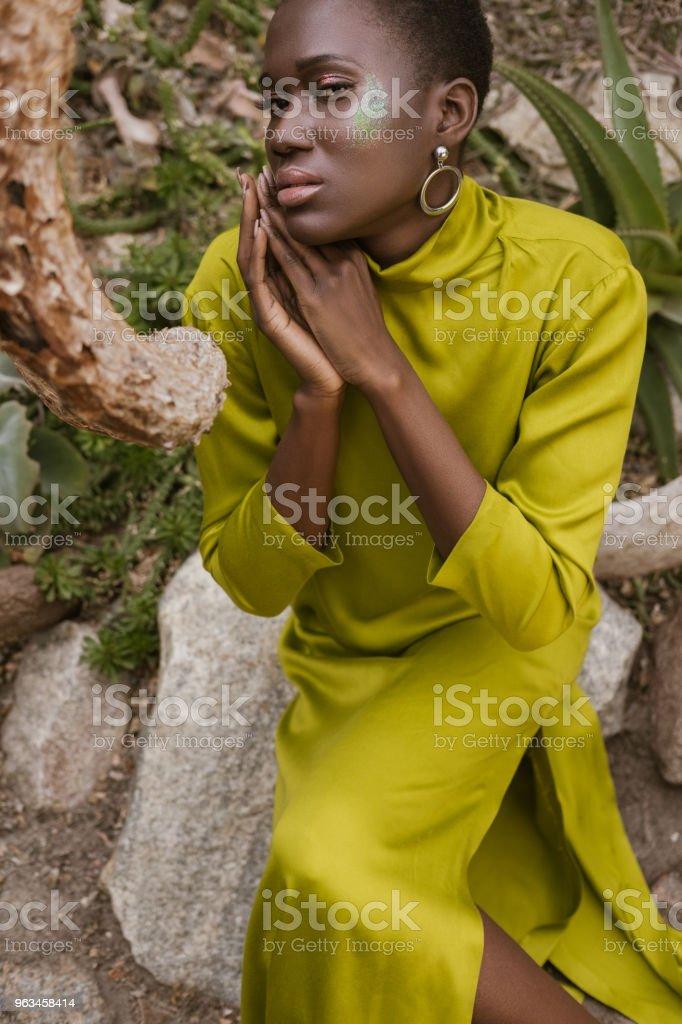 hermosa moda mujer afroamericana con maquillaje brillo posando en vestido amarillo - Foto de stock de A la moda libre de derechos