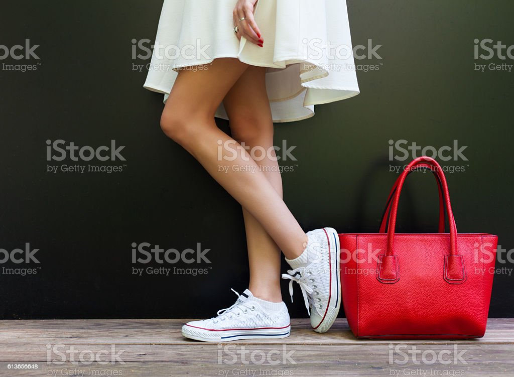 Beautiful fashionable big red handbag standing next to leggy woman Beautiful fashionable big red handbag standing next to leggy woman in white short dress and white sneakers. Part of body. Adult Stock Photo