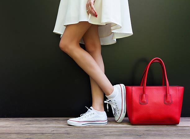 beautiful fashionable big red handbag standing next to leggy woman - joggingschuhe stock-fotos und bilder