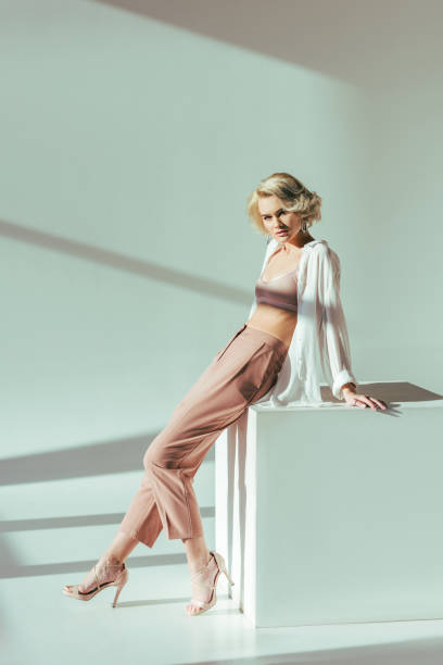 beautiful fashionable blonde woman in pink bra, shirt and pants sitting and looking at camera in studio beautiful fashionable blonde woman in pink bra, shirt and pants sitting and looking at camera in studio lingerie stock pictures, royalty-free photos & images