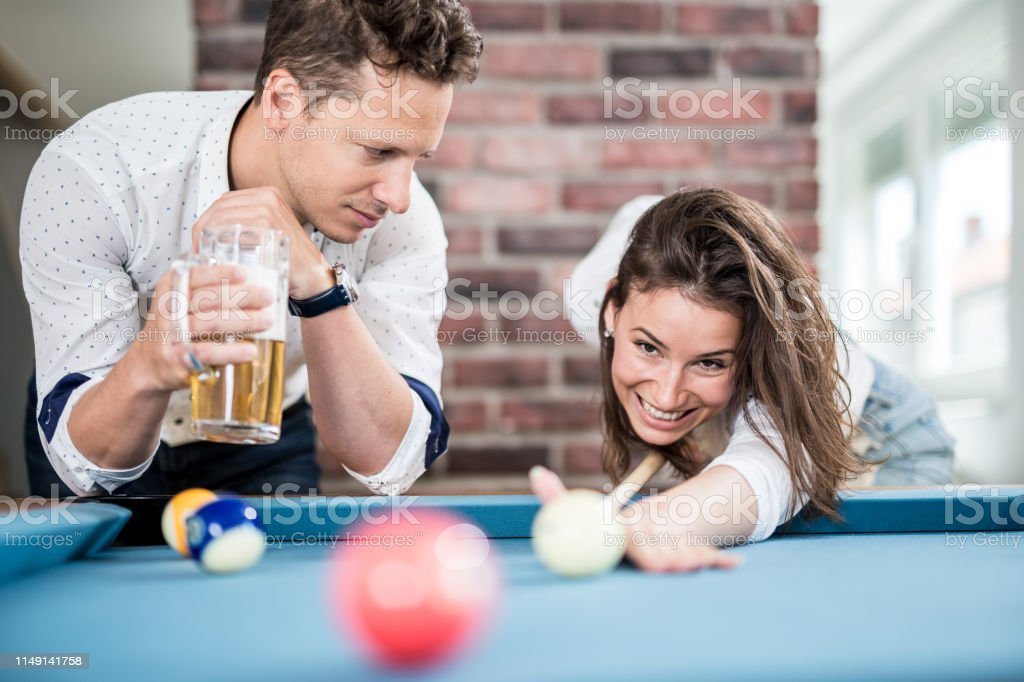 Couple playing snooker game and drinking beer.