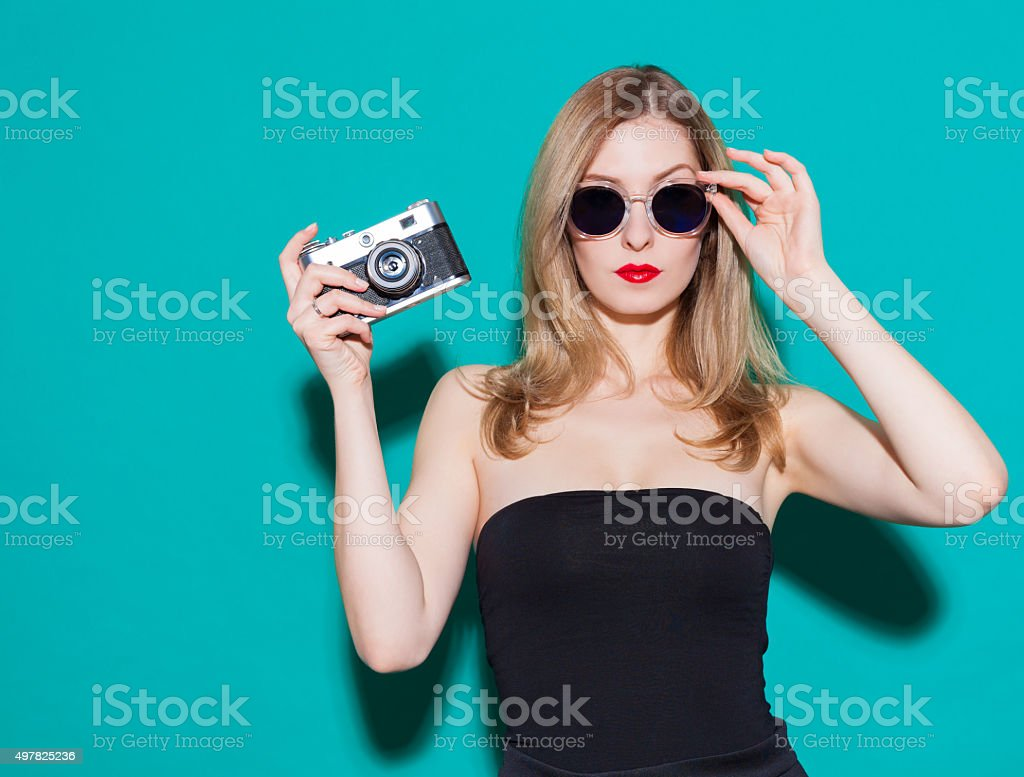 Beautiful fashionable girl posing and holding a vintage camera stock photo