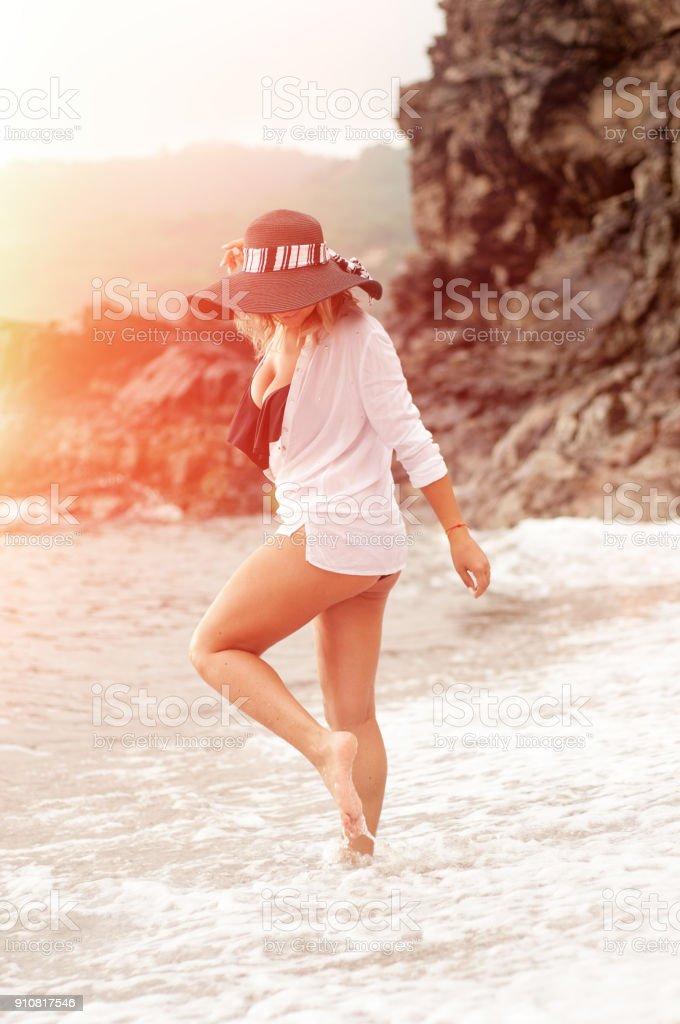 c090fd8fee Garota bonita e elegante com um chapéu, fato de banho e uma camisa branca na