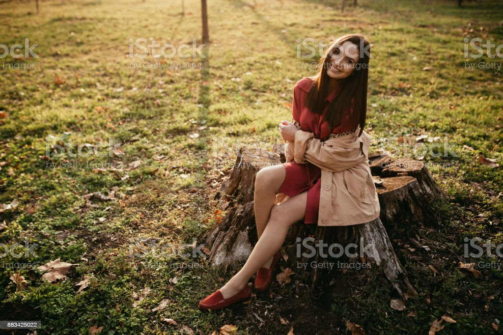 Beautiful fashionable woman in the public park on a lovely sunny day stock photo