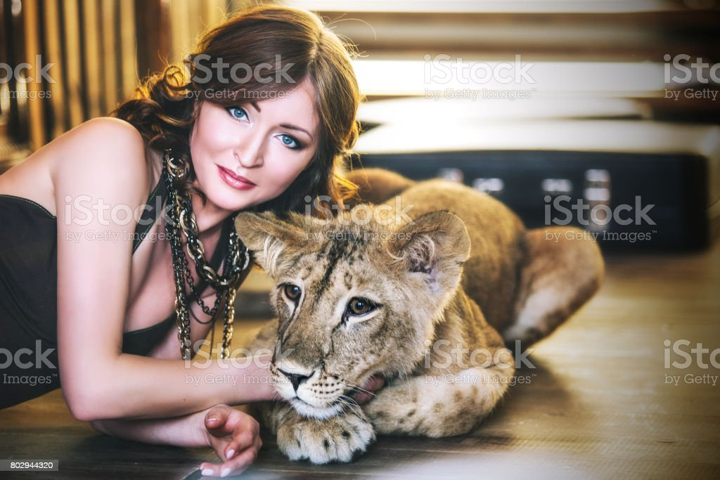 Beautiful fashionable young woman with a little alive lion cub stock photo