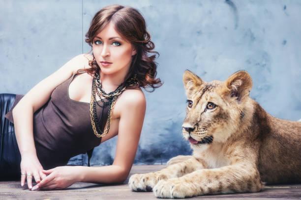 Belle jeune femme à la mode avec un petit lionceau vivant - Photo