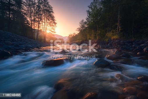 Beautiful fast river flows in mountain forest at sunrise