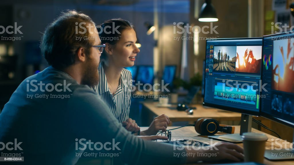 Beautiful Female and Handsome Male Video Editors Discuss Footage They're Working On. They Enjoy Working Together in a Cozy Creative Studio. stock photo