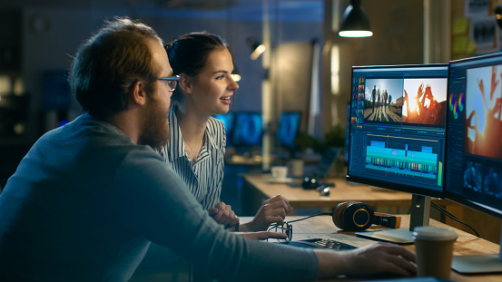 Beautiful Female And Handsome Male Video Editors Discuss Footage Theyre Working On They Enjoy Working Together In A Cozy Creative Studio Stock Photo - Download Image Now