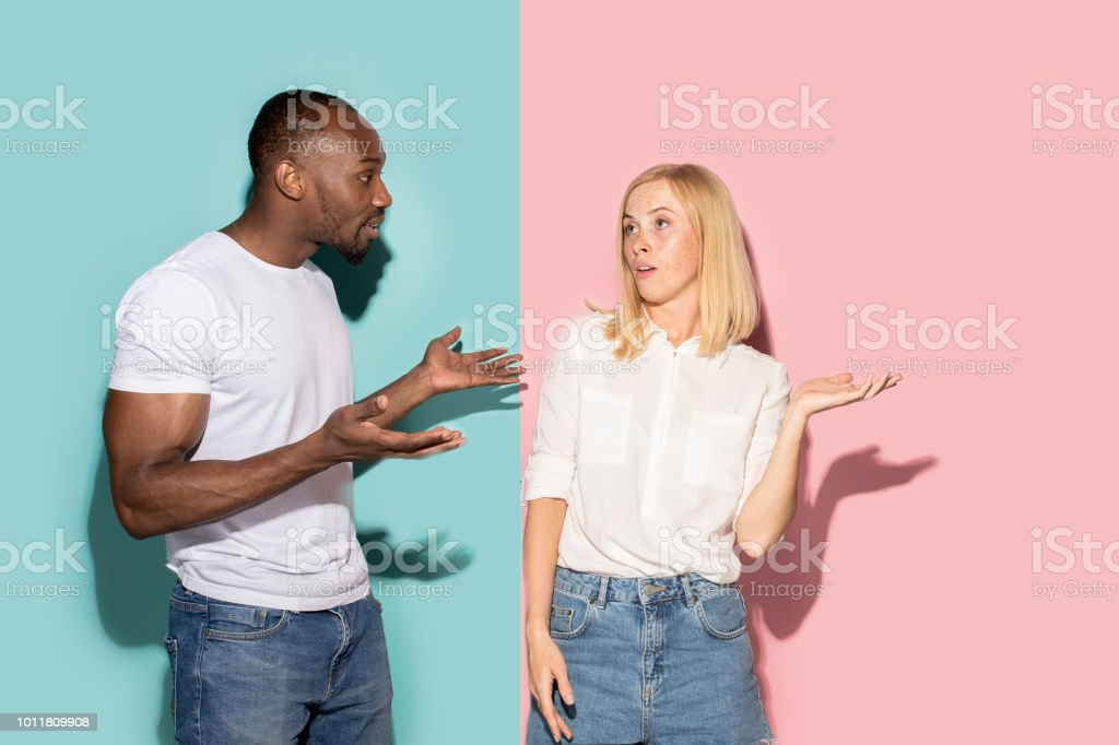 Beautiful female and male portrait on pink and blue studio backgroud. The young emotional couple stock photo