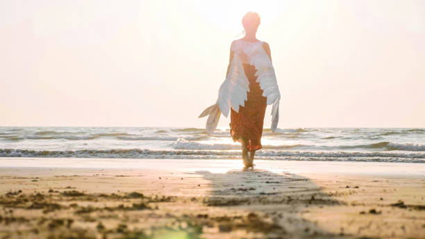 Beautiful female angel walking barefoot toward the sea at sunset. Beautiful female angel walking barefoot from camera toward the sea at sunset, rear view angelic stock pictures, royalty-free photos & images