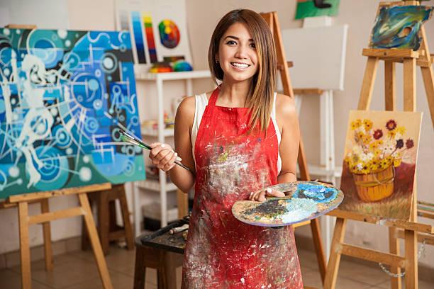 schöne weibliche künstler in ihrem studio - künstler stock-fotos und bilder