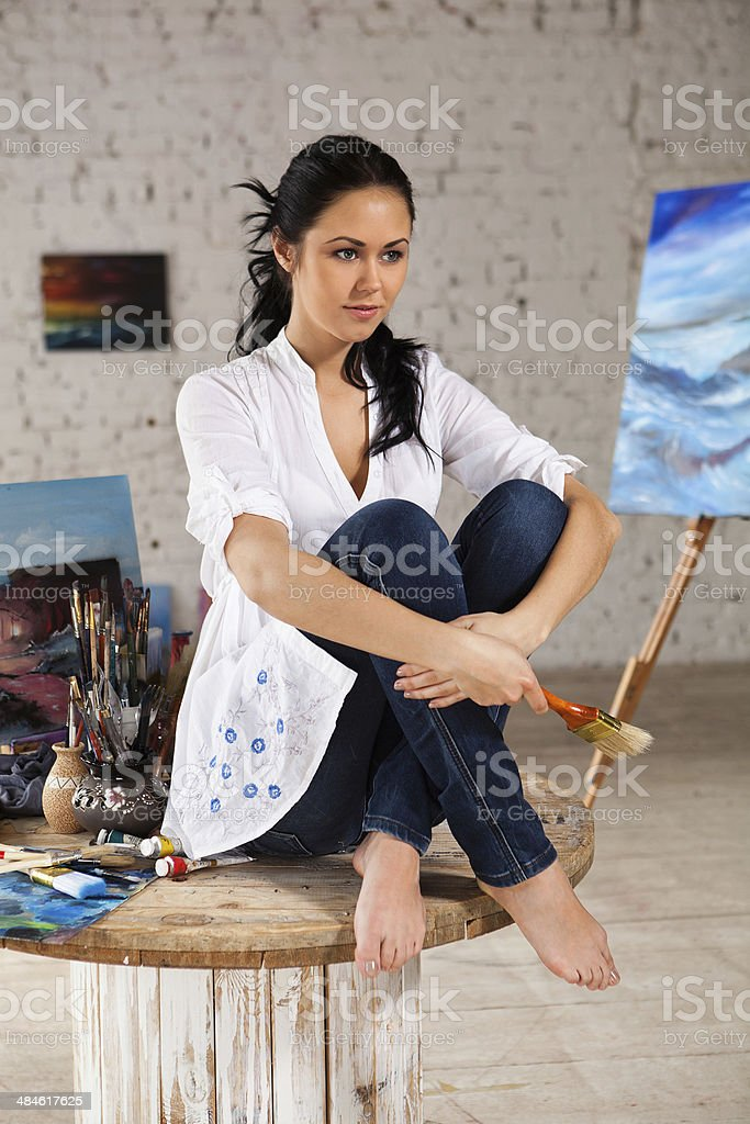 Beautiful female artist sits in her art studio stock photo