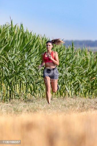 Beautiful female athlete running fast in nature near corn field