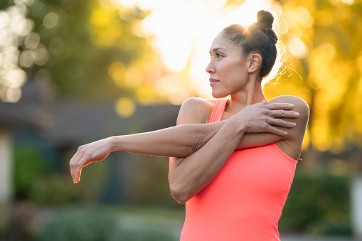 An athletic Pacific Islander woman smiles while doing warm up exercises and stretches outside before going for a run on a sunny day.