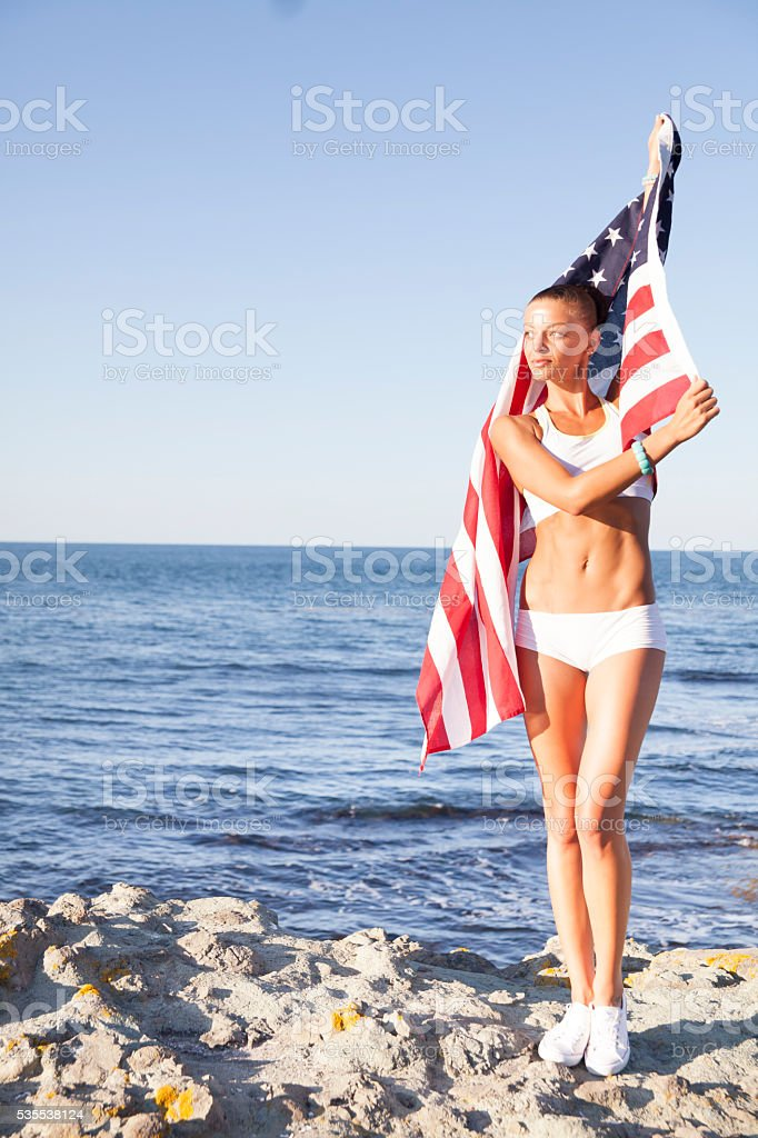 Beautiful female athlete waving the USA flag at beach stock photo