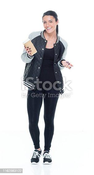 Beautiful female athlete wearing bomber jacket, leggings, sport shoes