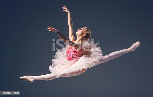 istock Beautiful female ballet dancer on a grey background. Ballerina is 533579793
