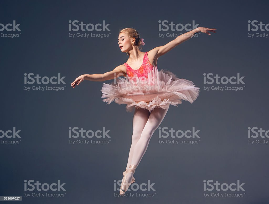 Beautiful female ballet dancer on a grey background. Ballerina is stock photo