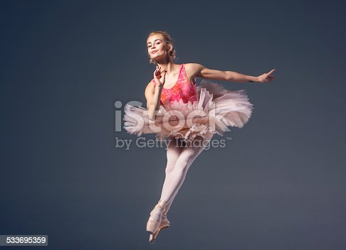 476021886 istock photo Beautiful female ballet dancer on a grey background. Ballerina is 533695359