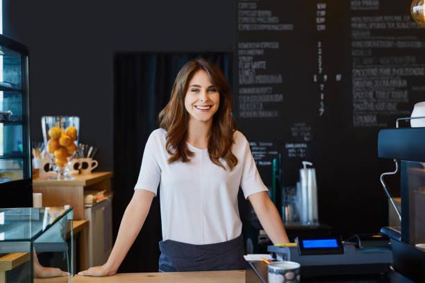 belle femelle barista debout derrière le bar à café - directrice photos et images de collection