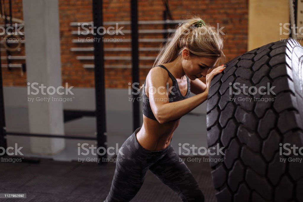 beautiful female bodybuilder is flipping the tire in the sport center...