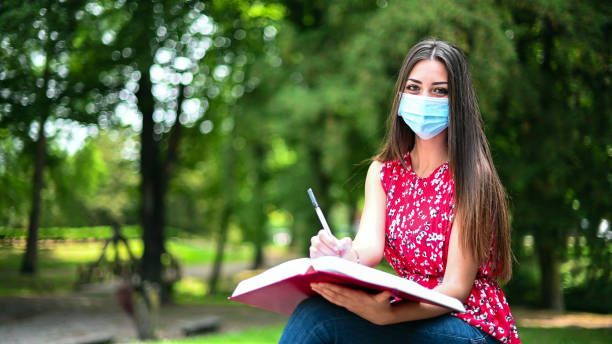 Beautiful female college student reading a book on a bench in a park and wearing a mask in coronavirus times stock photo