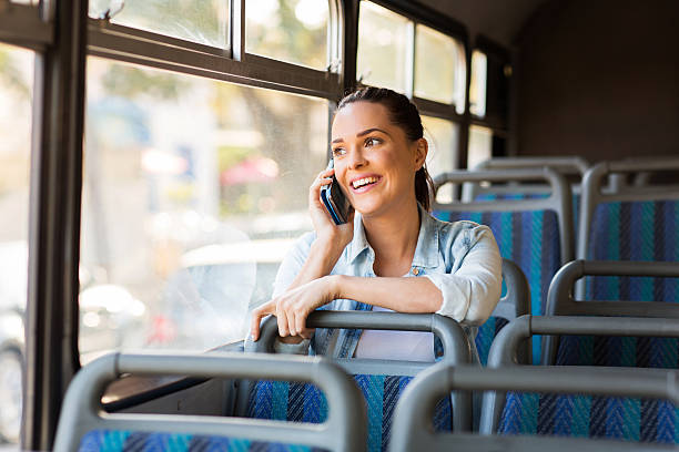 beautiful female commuter talking on cell phone stock photo