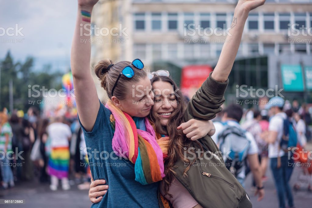 Beautiful female couple hugging while marching on the street stock photo