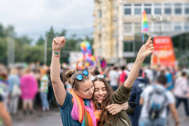 Beautiful female couple hugging while marching on the street Young excited females walking on the city street, laughing and hugging marching stock pictures, royalty-free photos & images