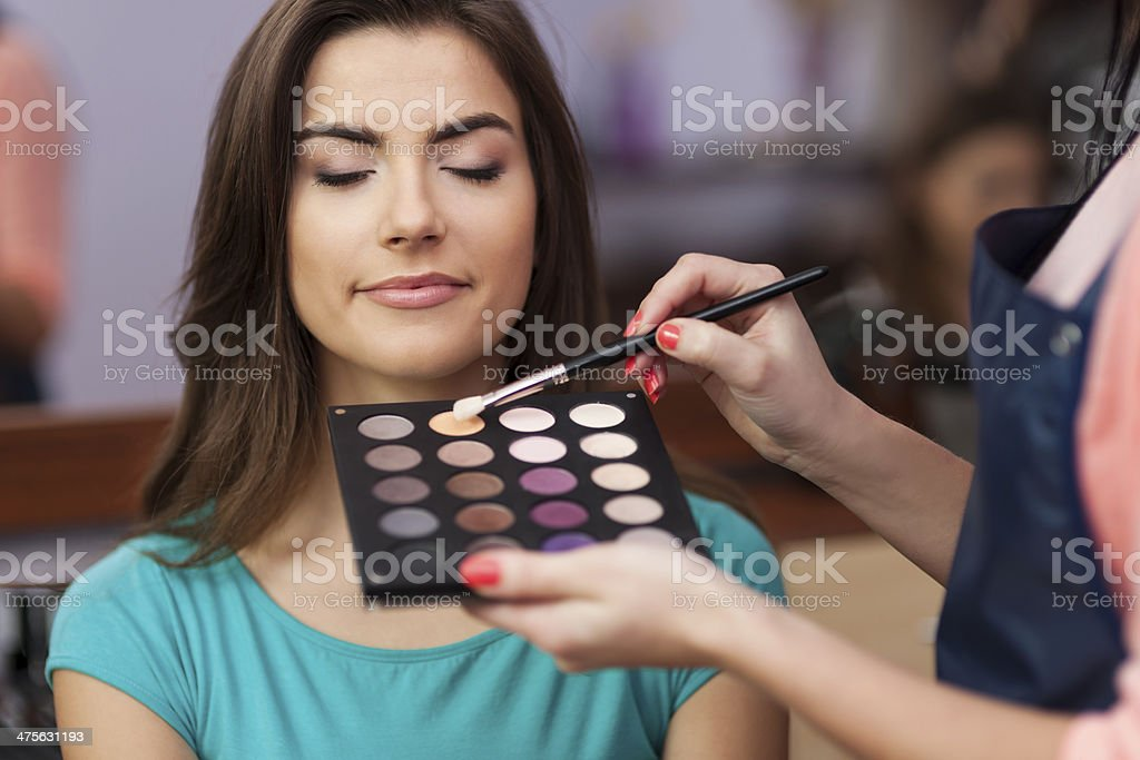 Beautiful female customer during the work of makeup artist stock photo
