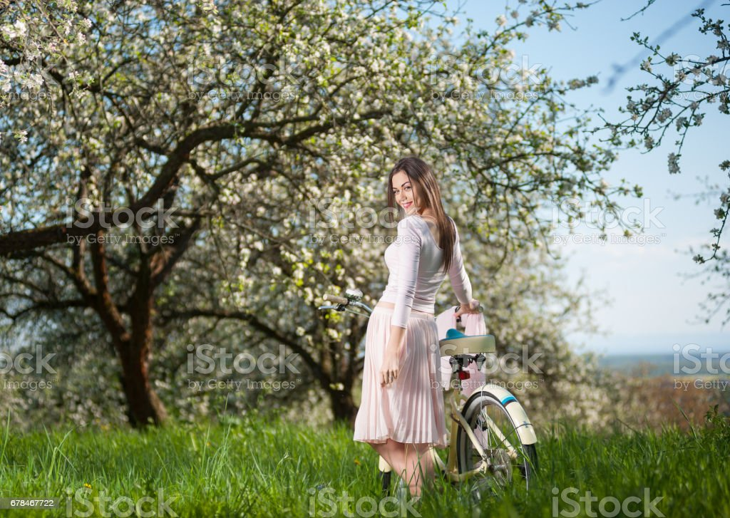 Beautiful female cyclist with retro bicycle in the spring garden royalty-free stock photo