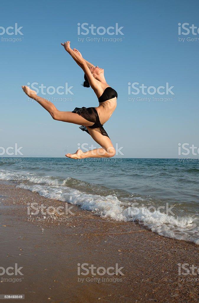 Beautiful female dancer jumping  on a beach stock photo