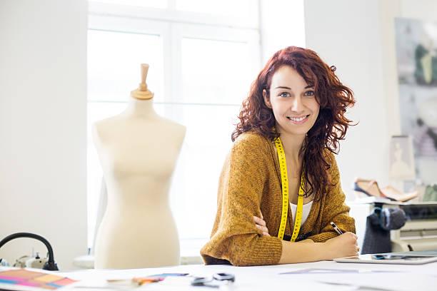 Beautiful female designer at design studio Beautiful young female designer sitting at a table in clothing design studio fashion designer stock pictures, royalty-free photos & images