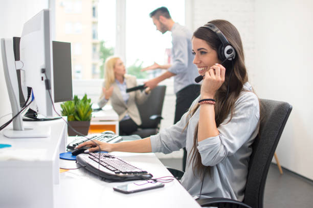 Beautiful female dispatcher with hands-free headset helping a client via online video or audio call. stock photo