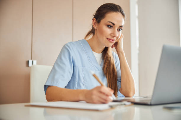 Beautiful female doctor working on her laptop stock photo