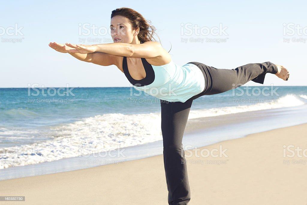 Beautiful female doing yoga at the beach royalty-free stock photo